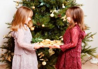 GirlsInFrontOfChristmasTree holiday gifts